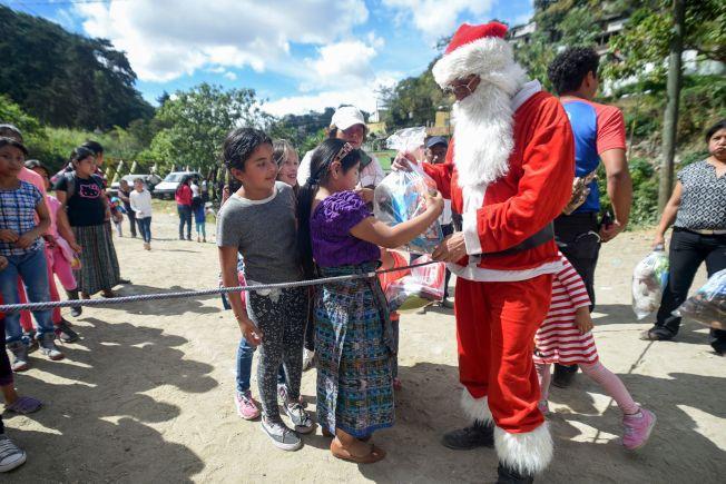 瓜地馬拉消防員Hector Chacon扮成耶誕老公公從橋上拉著吊繩從天而降,為孩子送禮物。(Getty Images)