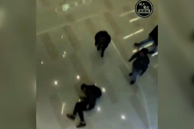 有香港民眾因逃避防暴警察追捕,從商場二樓高處躍下墜落地面。(科大電台片段截圖)