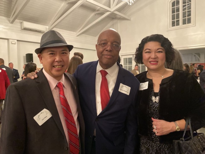 耶誕招待會主要贊助人陳海娜與陳志光與北卡民權領袖亨德生(Clarence Herderson)合影。(陳海娜提供)