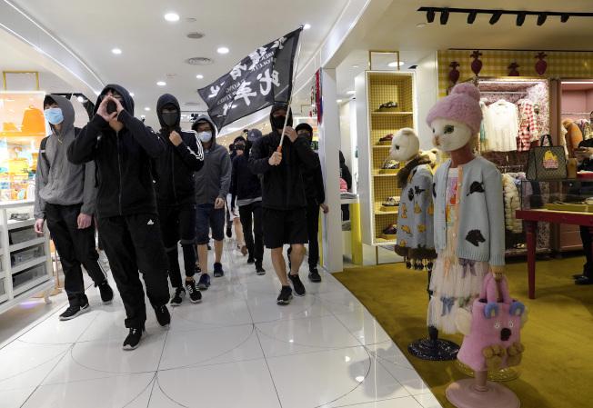 香港示威者26日又在多個商場聚集,他們舉著黑色旗幟,高喊「反送中」口號。(美聯社)