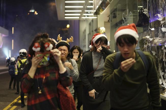 圖為香港民眾24日上街慶祝耶誕活動,遭遇警察施放催淚彈。(美聯社)