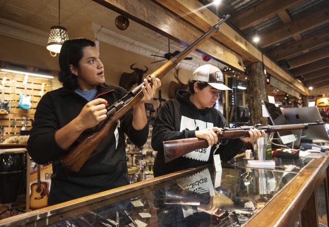 加州在明年的新法將限制每月購槍的數量,圖為顧客在槍店選購。(美聯社)