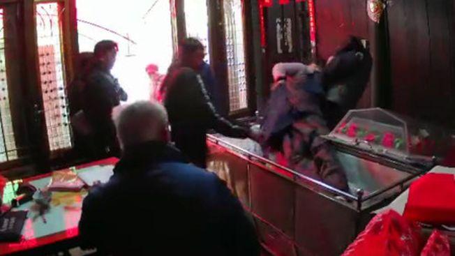 死者子女突然闖進喪禮,將父親的遺體從棺材裡拖拉出來,又是搧臉、又是用腳狂踹。( 視頻截圖)