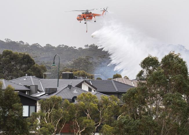 滅火飛機從數個社區上空飛過,居民也拿水管替房屋澆水,盼能阻止火勢蔓延。(歐新社)