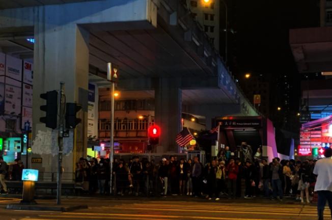 太子站C1出口外有大批香港民眾聚集。有人高舉美國和英國國旗,及播放佛經音樂。取材自香港電台