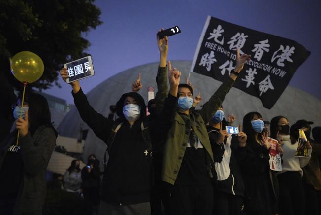 除夕夜香港持續有反送中活動。圖為抗議者舉起「光復香港、時代革命」的旗幟。美聯社