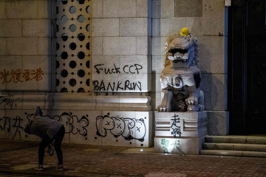 港人8日舉行「國際人權日遊行」,一人彎下身拍攝中國銀行門前的塗鴉。(Getty Images)