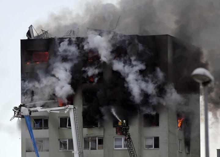 大火濃煙已經將公寓大樓外墻熏黑,消防員緊張援救。(美聯社)