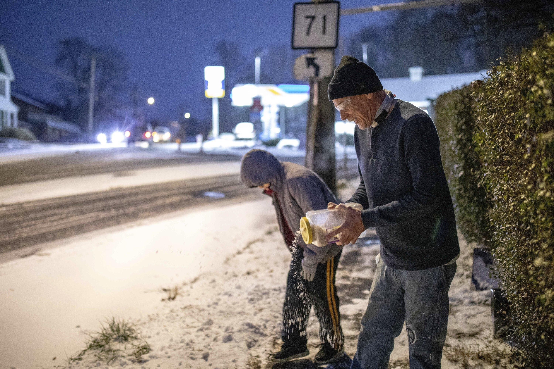 1日,康州居民在人行道上撒鹽融雪。感恩節周末全美多處狂風暴雪,給節後上班的通勤者帶來不便。(美聯社)