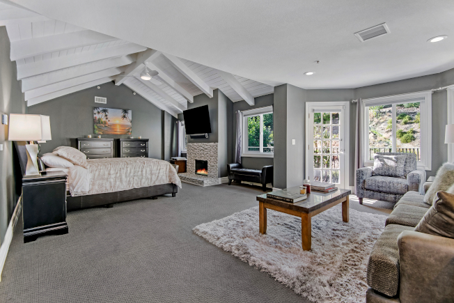 樓上的主臥室擁有造型天花板、休憩區域、壁爐、兩個衣帽間、以及巨大的浴室。(Realtor)