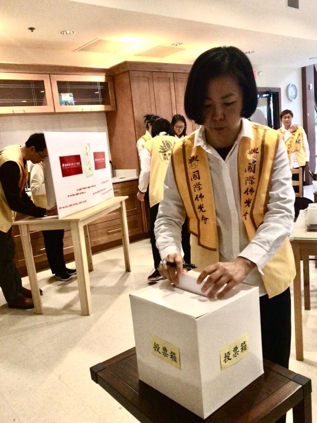 會員在隔離的投票亭圈選候選人後,將選票投入投票箱中。(記者王明心/攝影)