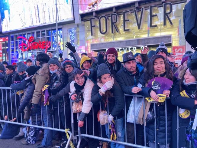 時報廣場上的民眾,紛紛伸手索取2020年跨年紀念帽。(記者張晨/攝影)