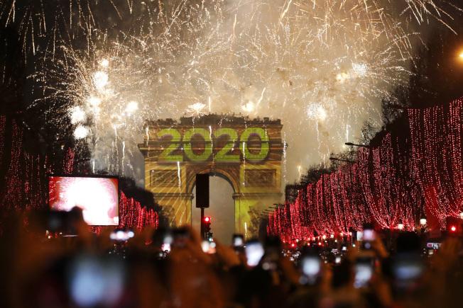 圖為巴黎香舍麗榭大道的彩燈及凱旋門的煙火。(美聯社)