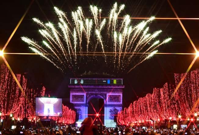 圖為巴黎香舍麗榭大道的彩燈及凱旋門的煙火。(Getty Images)