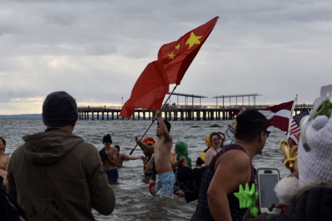 繆子泉高舉著中國國旗下水,很開心自己又完成了新一年的挑戰。(記者顏潔恩/攝影)