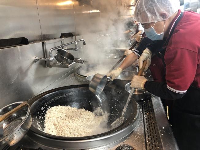 後廚義工在辛苦的攪拌粥。(記者張宏/攝影)