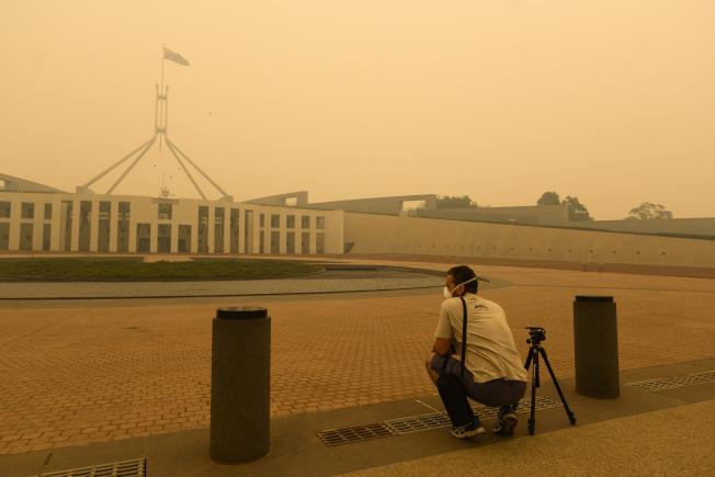 澳洲首都坎培拉的國會大樓也籠罩於滾滾黃煙之中。(Getty Images)