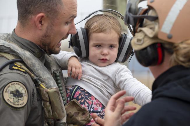 澳洲國防部官員從深受山火影響的地區救出民眾。圖中,一軍官給小孩戴上降噪耳機。目前,澳洲山火蔓延範圍之廣,已達馬里蘭州兩倍大。(美聯社)
