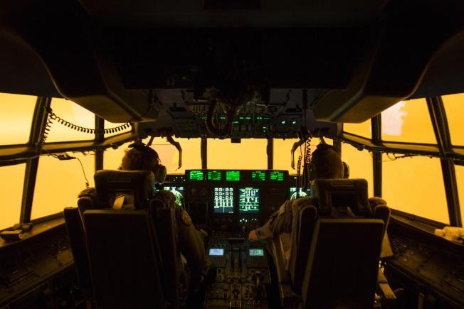 澳洲國防部的一架救援軍機上,機組人員正前往火災現場。機窗外一片橘黃,濃煙蔓延。(美聯社)