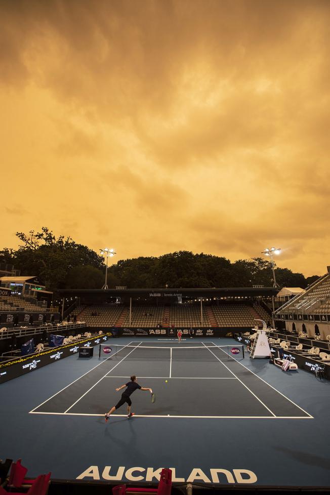鄰國紐西蘭也深受影響。圖中,紐西蘭城市奧克蘭一座網球場上方的天空已經變成橘色。(美聯社)