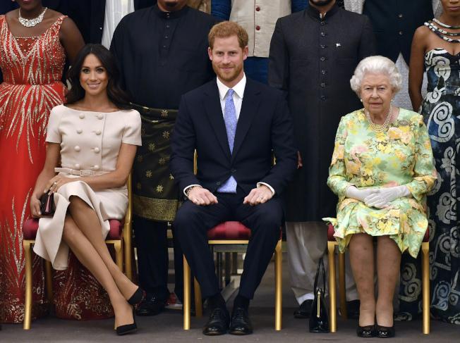 英國哈利王子夫婦宣布,將從王室高級成員身分引退,並在北美和英國兩地居住。圖為哈利王子夫婦出席王室活動時,坐在女王身邊。(美聯社)