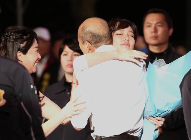 韓國瑜夫人李佳芬(左)、女兒韓冰(擁抱白襯衣者)在造勢活動現場為韓(白襯衣者)加油。(中新社)