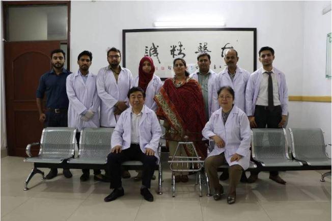 喇傑廉(前排左)和他的中醫醫院。(取材自紅星新聞)