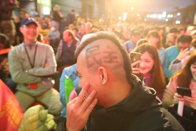 蔡英文總統連任成功,支持者欣喜若狂。其中一名支持者還在頭髮上雕出「民主」二字。記者陳柏亨/攝影