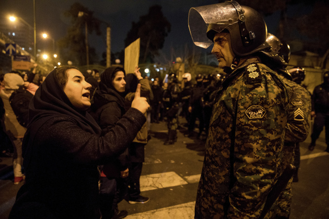 伊朗隱瞞擊落客機,民怨沸騰;圖為示威學生手指軍隊大聲抗議。(美聯社)