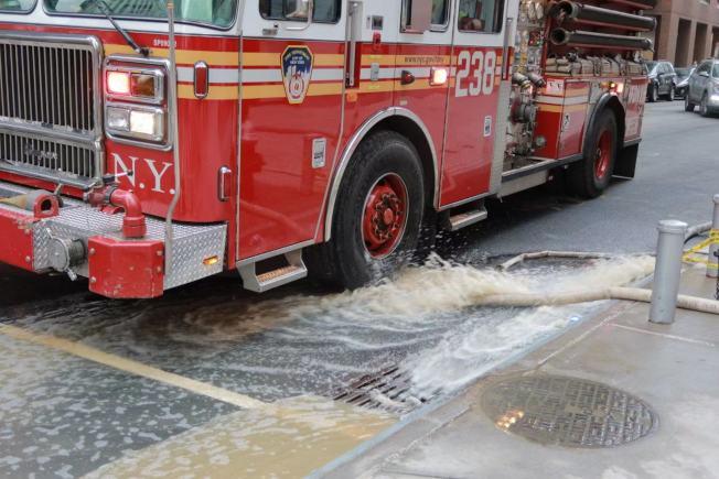 水管爆裂排出的水傾瀉至路面。(記者張晨/攝影)