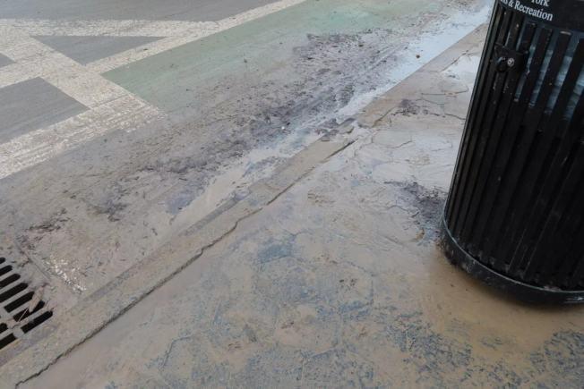 積水褪去後路面泥濘不堪。(記者張晨/攝影)