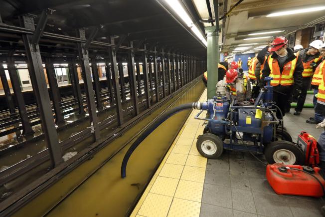 工作人員在地鐵站中排水。(美聯社)