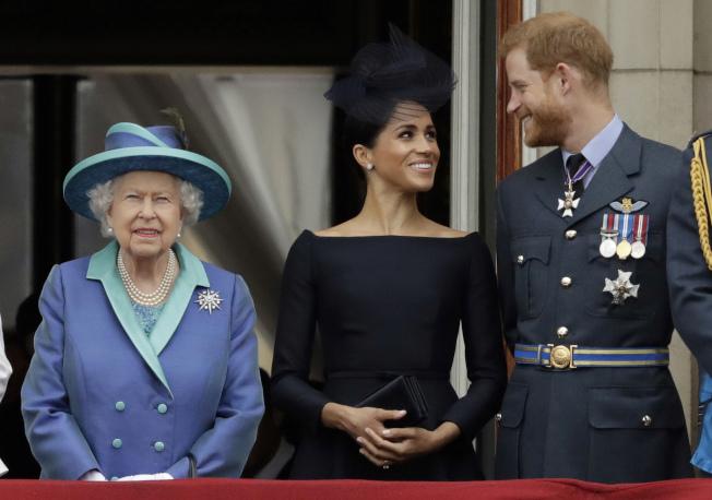 女王伊莉莎白二世與哈利王子、新婚妻子梅根王妃,2018年7月在倫敦白金漢宮的陽台上觀賞皇家空軍的飛行特技表演。(Getty Images)