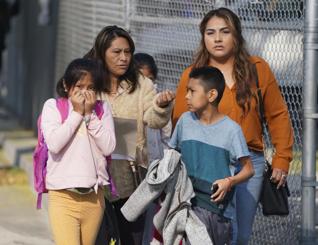 事件發生後,家長帶小孩離開學校,一名女童用衣服遮口鼻。(美聯社)