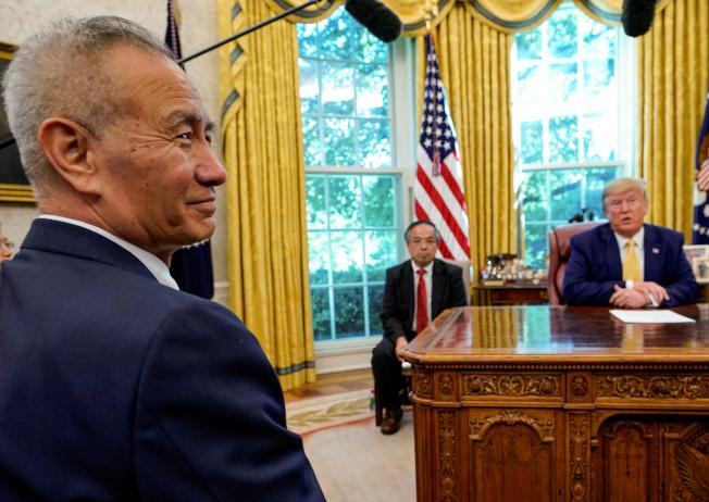 美中簽訂第一階段貿易協議,但美國對中國進口商品暫時不再降低關稅,圖為川普總統(右)去年10月在白宮接見中國國務院副總理劉鶴。(路透)