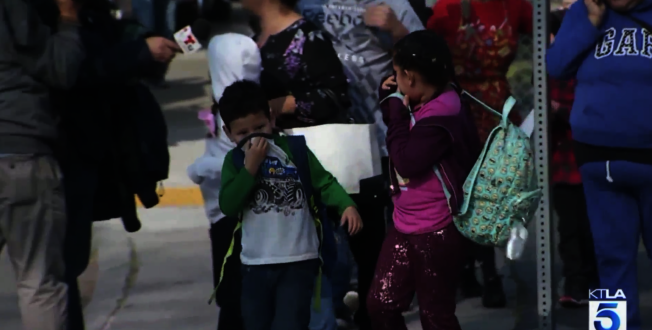 受影響學校的學生離開學校時,因周遭燃油氣溫濃,用衣服捂臉。(取自KTLA)
