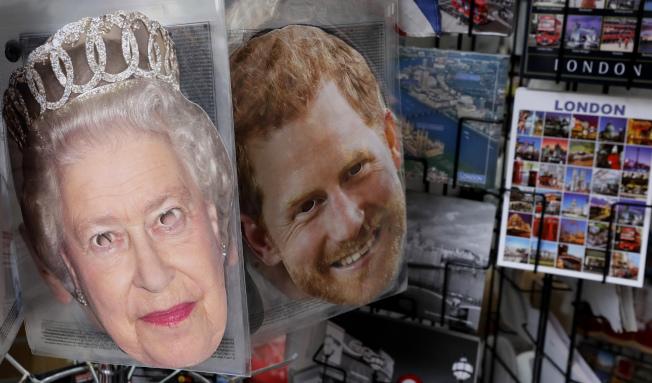 英國王室的的嫌隙浮上檯面,主角哈利王子與女王的大頭照被製作成面具14日擺在倫敦的禮品店門口。(美聯社)