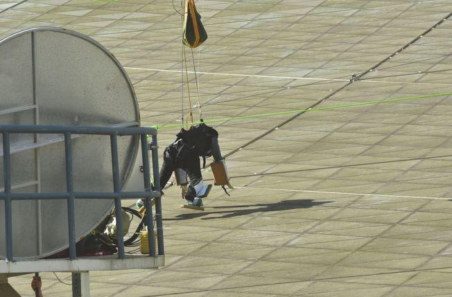 工作人員在望遠鏡反射面上「行走」時,利用氦氣球的浮力能夠將人的重量降到反射面結構可以承載的重量。(取材自華西都市報)