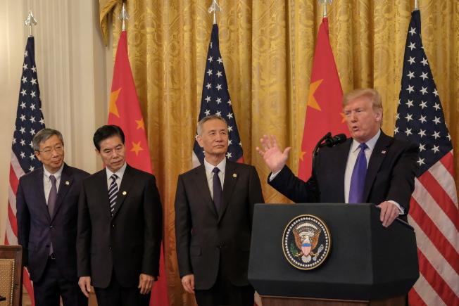 川普總統(右)在簽字前發表冗長談話,中國國務院副總理劉鶴(左三)率領的中方代表團在旁枯等。(歐新社)