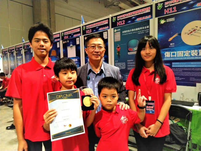 鄧鴻吉(中)和澳門國際發明展台灣得獎學生合影。(本報資料照片)