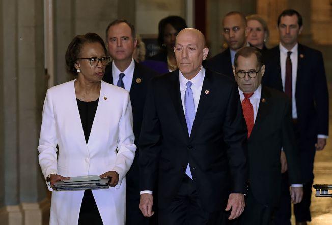 眾院議長波洛西簽署彈劾案文書後,由七名彈劾經理護送,交給參院。(Getty Images)