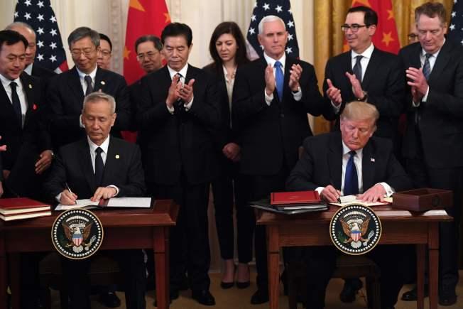 美中兩國在白宮簽署第一階段貿易協議,由川普總統(前右)和中國國務院副總理劉鶴(前左)代表雙方簽字。(Getty Images)