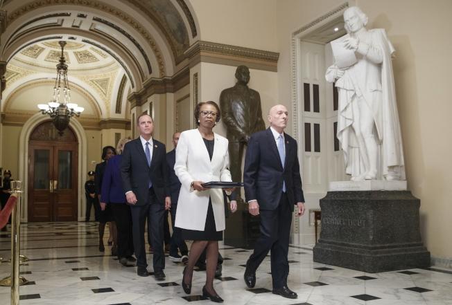 眾院議長波洛西簽署彈劾案文書後,由七名彈劾經理護送,交給參院。(歐新社)