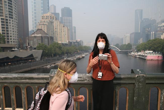 煙霧籠罩 墨爾本昨被野火煙霧籠罩,路人紛紛戴起口罩拯救自己的肺。(歐新社)