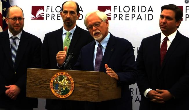 州長德桑提斯(Ron DeSantis, 右一)和佛州預大學委員會主席路得(John Rood, 右二)於1月13日宣布預付大學學費計畫的價格降低13億元。(影片截圖)