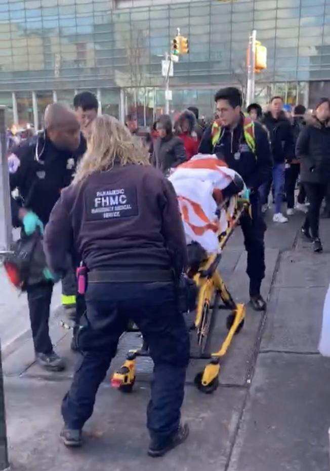 醫護人員把被砸的華女抬上救護車。(讀者提供)