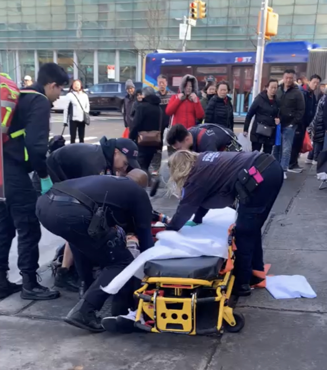 被砸的華女倒在地上,醫護人員趕來搶救。(讀者提供)