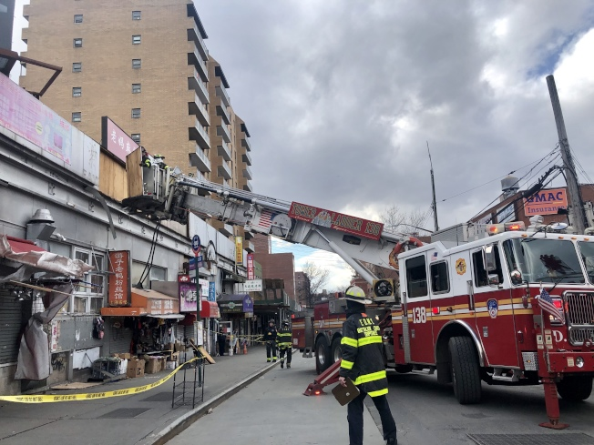 事發現場被封鎖,消防員檢查大樓外部。(記者朱蕾/攝影)