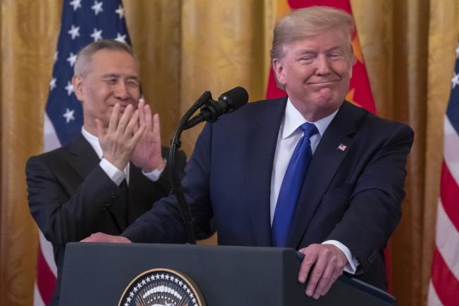 美中簽署第一階段貿易協議,川普總統(右)在儀式上興奮致詞,中國國務院副總理劉鶴在旁鼓掌。(歐新社)