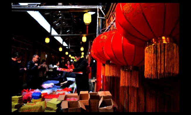 中國去年人均GDP正式突破1萬美元大關。圖為湖北省恩施土家族苗族自治州宣恩縣慶陽古街,民眾在採購年畫和燈籠迎接春節到來。(新華社)